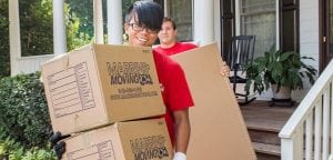 Two Marrin's Moving employees carrying cardboard boxes and smiling
