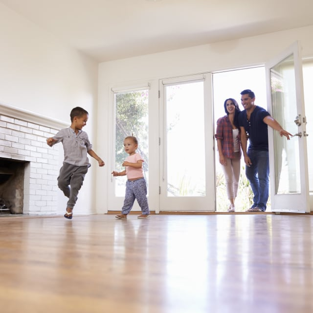 A young family of four excitedly moving into a brand new house with hardwood floors and white walls