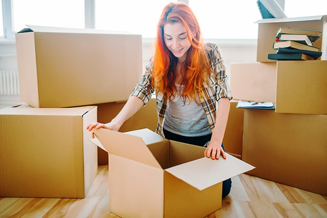Young female college student excitedly opening a cardboard box to move in to her new dormroom