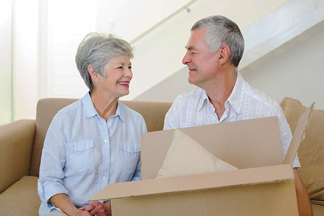 Older couple smiling at each other, holding a cardboard box in preparation for a move