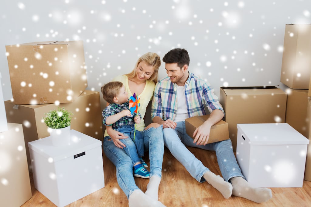 Young family of three sitting on the floor surrounded by unopened cardboard boxes